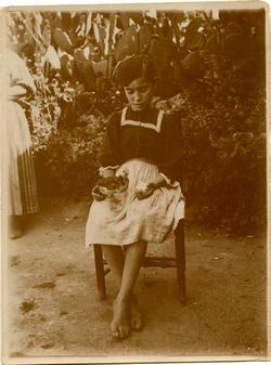 m.-Niña sentada con un pollito en la mano