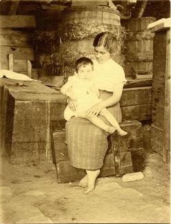 o.-Mujer pescadora sentada con el niño en brazos