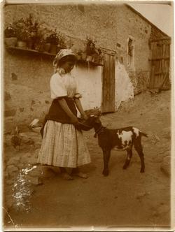 p.-Mujer joven alimentando a un cabritillo
