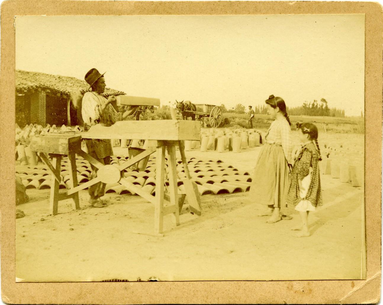 q.-Albañil haciendo teja con los galápagos. Niñas observando